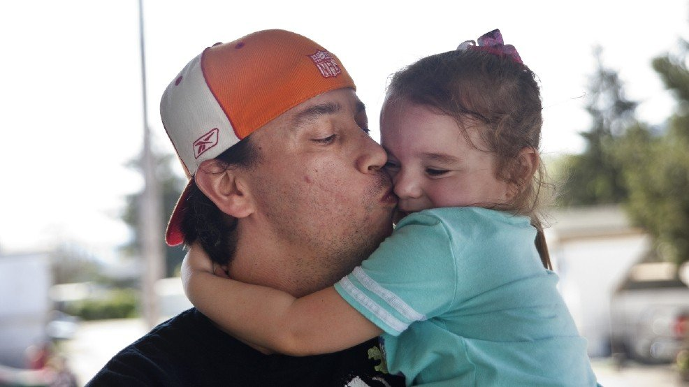 In this photo taken Saturday April 2, 2016, Bryan Thouvenel gives his daughter Harmony Thouvenel, 5, a kiss while standing for a portrait in front of their home. (Katie Alaimo/The News-Review via AP)
