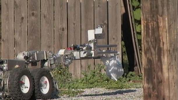 Bomb robot carrying suspected device to bomb disposal unit