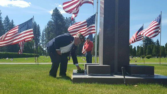 Vietnam veteran Doug Park places flowers on a Spokane memorial