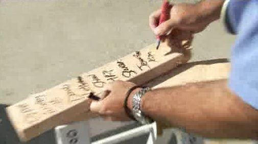 Wrestler signs the boards and gives them to those who donate to his foundation