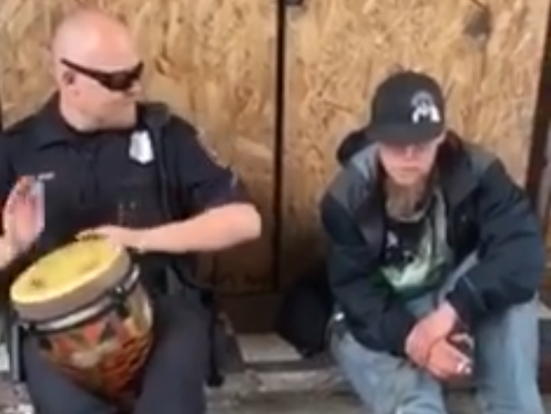 Officer Casey Jones plays the drum with a street performer downtown.