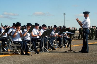 Maj. Keith Bland (right), conductor/commander of the Air Force's Band of the Golden West leads direction of the band as they play during the opening ceremonies for Air Mobility Command's RODEO 2009 July 19 at McChord Air Force Base, Wash.