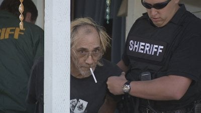Michael Craig McGuire, 55, is led out of his home by the Spokane County Sheriff's office