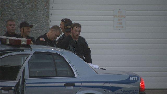 Wanted fugitive Jeremy A. Hagen being taken into custody