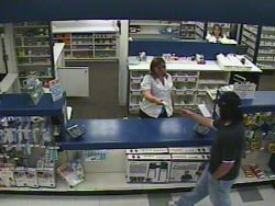 The suspect takes a bottle of prescription drugs from the pharmacist in the August 24 ShopKo pharmacy robbery
