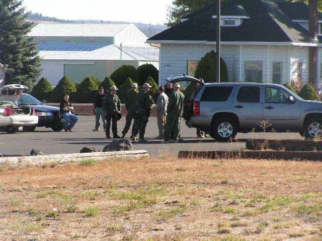 Law enforcement stages at Goldendale High School preparing to search for Paul