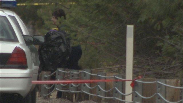 Investigator carrying black plastic bag found near the body