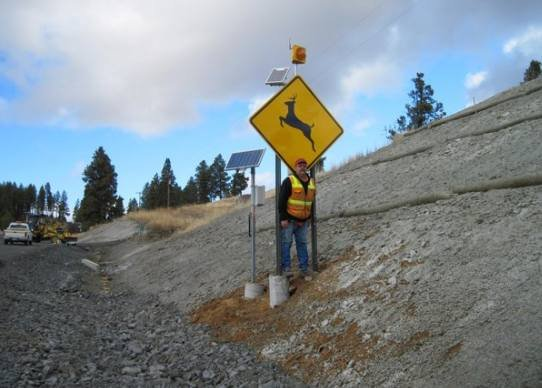 Idaho Transportation Department inspector Mike Cameron stands next to the new wildlife warning system on U.S. 95 at Moscow Mountain. Photo: Spokesman-Review