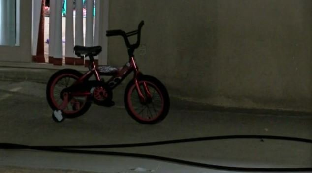 A bike sits outside the home where a 5-year-old boy, a 6-year-old girl and a 9-year-old boy were shot and killed by a gunman who police believe had a relationship with their mother for a short time.