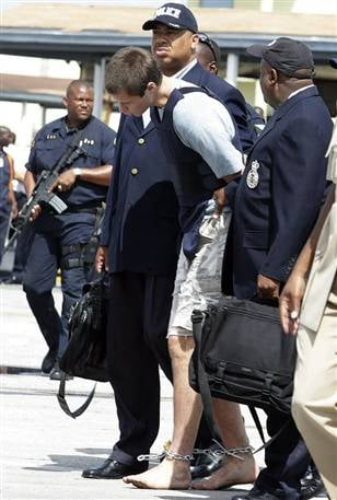(Courtesy MSNBC; Colton Harris-Moore arrives barefoot, handcuffed and shackled as he is escorted by police to Nassau on Sunday)