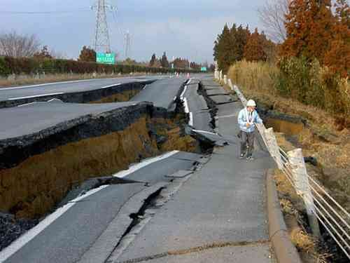 A worker inspects a caved-in section of the Joban Motorway near Mito, Ibaraki Prefecture after the quake