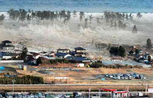 Tsunami tidal waves hit houses after a powerful earthquake in Natori