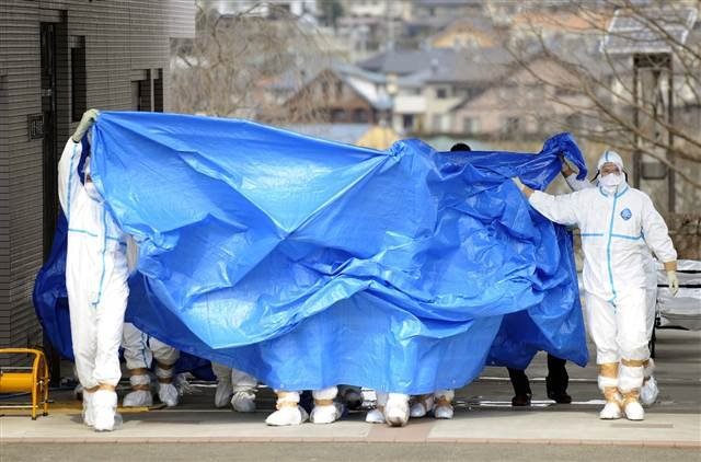 Workers from the Fukushima Dai-ichi nuclear complex are shielded with tarps before receiving decontamination treatment at a hospital on Friday