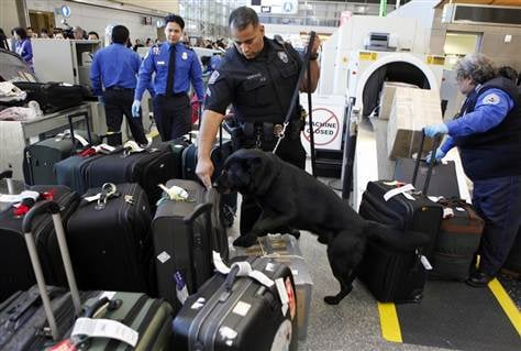In this Jan. 5, 2010 file photo, Los Angeles International Airport (LAX) Enforcement Special Unit police officers use a bomb-sniffing dog to check baggage at the Tom Bradley International Terminal