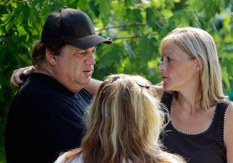 Sam Mazzola, left, is comforted by Ellen Vajda outside Mazzola's exotic animal sanctuary in Columbia Station, Ohio, on Aug. 20, after a bear fatally mauled a caretaker.