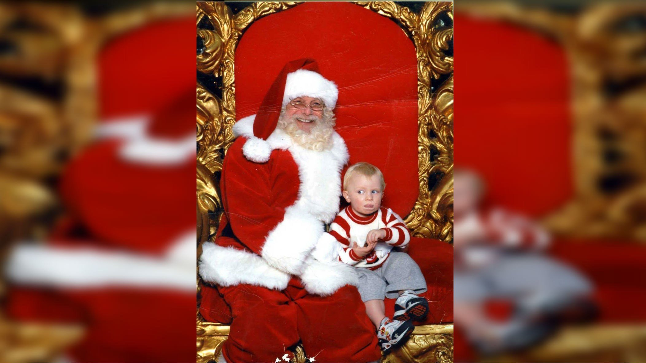 Toddler signs 'help' while sitting on Santa's lap