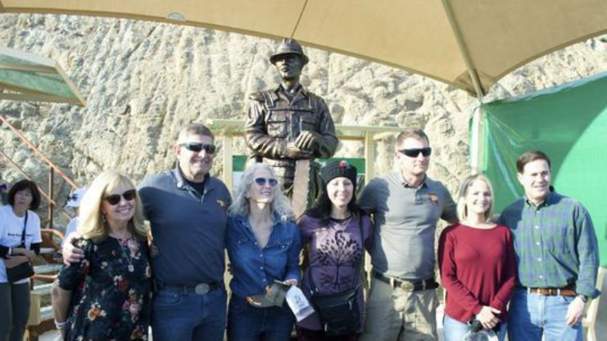 Judy Willis, Darrell Willis, Deborah Pfingston, Colleen Sinclair, Alan Sinclair, Roxanne Preston and Gov. Doug Ducey take a photo at the surprise unveiling of a statue to honor wildland firefighters at the Granite Mountain Hotshots Memorial State Park.
