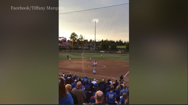 Softball crowd sings national anthem on their own