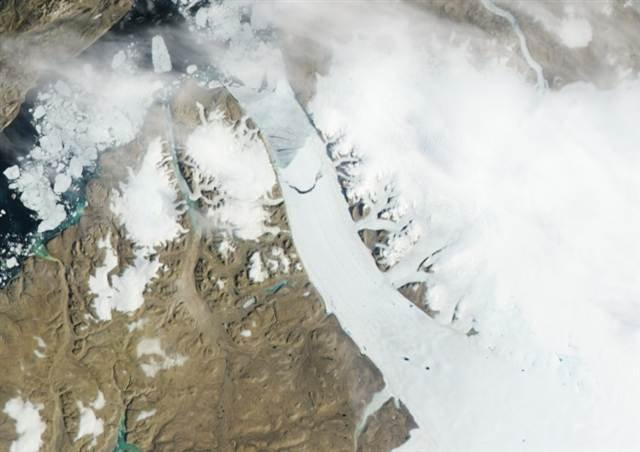 This satellite image from Monday shows an iceberg, top center, breaking off from the Petermann Glacier in northwest Greenland; Photo courtesy MSNBC