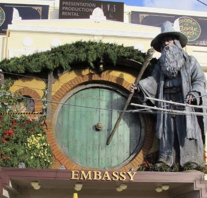 "People walk by the Embassy Theater where a giant statue of the character Gandalf from the upcoming movie ""The Hobbit: An Unexpected Journey"" overlooks the passersby in Wellington, New Zealand, Monday, Nov. 19, 2012."