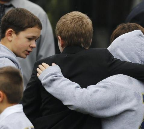 Students embrace while wearing Newtown school shirts outside the funeral for six-year-old student shooting victim Jack Pinto in Newtown, Conn., Monday, Dec. 17, 2012.