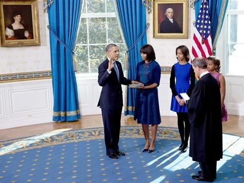 President Obama takes the oath of office as Michelle holds the bible in the Blue Room of the White House on Sunday.