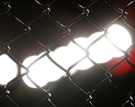 Lights shine on a chain link fence before a fight; Photo courtesy USA Today