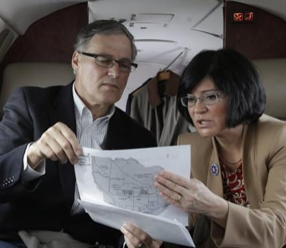 Washington Gov. Jay Inslee, left, looks at a map with Dept. of Ecology Director Maia Bellon, right, Wednesday, March 6, 2013