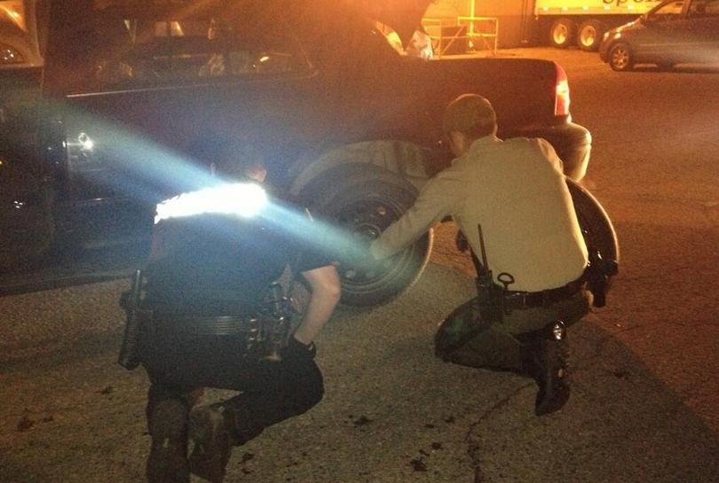 Officers inspect one of two patrol cars that broke down during the chase.
