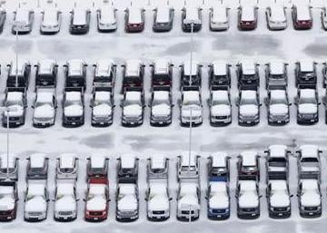 Ice covered vehicles sit in a automotive dealer lot Saturday in Lewisville, Texas.