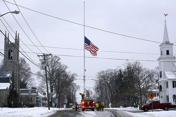 On the anniversary of the Sandy Hook Elementary School massacre, firefighters lower the town's flag on Main Street to half-staff in honor of the victims.