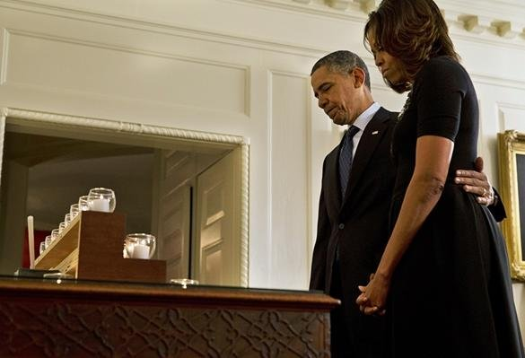 President Barack Obama and first lady Michelle Obama share a moment of silence in honor of the Newtown shooting victims on Saturday in the Map Room of the White House.