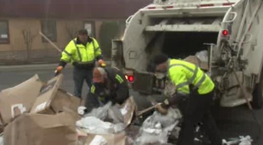 Workers clean up after finding two people in the back of the garbarge truck