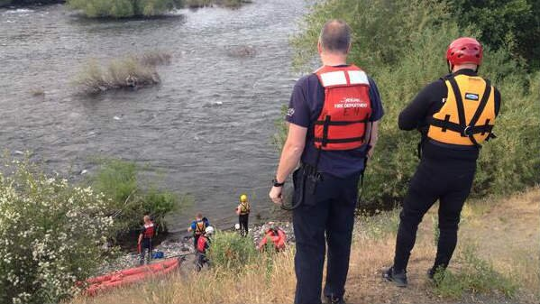 Firefighters pull a man clinging to a bush in the Spokane River Tuesday evening near People's Park