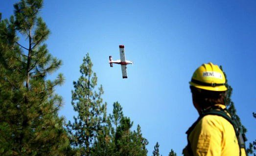 A firefighter watches an air crew fly over the Lake Spokane wildfire (PHOTO COURTESY: Stevens County Fire District #1)