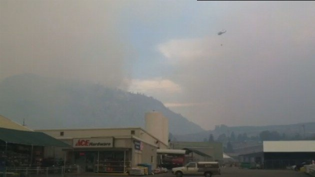 Fire crews called in a helicopter to drop water on the flames outside of Brewster on Friday.
