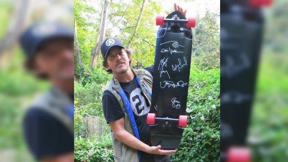 PHOTO: Eddie Vedder holding the skateboard signed at the Spokane concert (courtesy: eBay/Figurado)