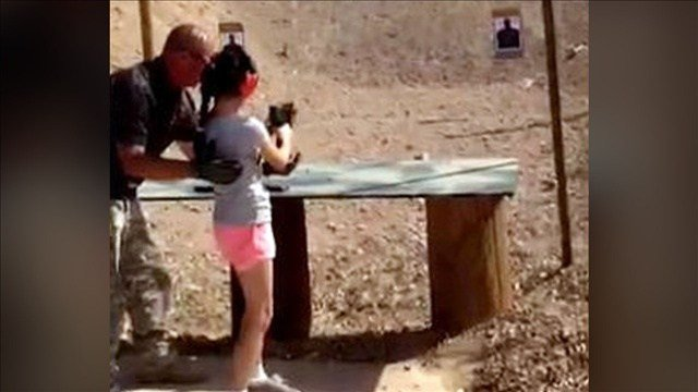 PHOTO: Charles Vacca, teaches the 9 year old girl how to handle the Uzi, Photo Credit: Mohave County Sheriff / AZfamily, Photo Date: 2014
