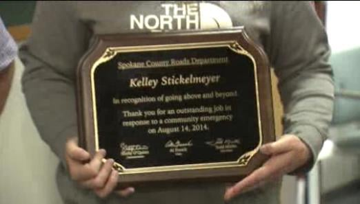 Kelley Stickelmeyer shows off her plaque, congratulating her for actions above and beyond