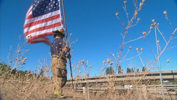 For 12 years straight, Spokane Firefighter Alex Mickschl has walked up the hill next to the Interstate with his flag and waved it proudly for everyone driving by to see.