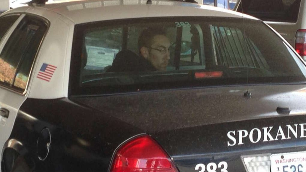 One of the three men detained in connection to two armed robberies on Tuesday sits in the back of a Spokane police car.