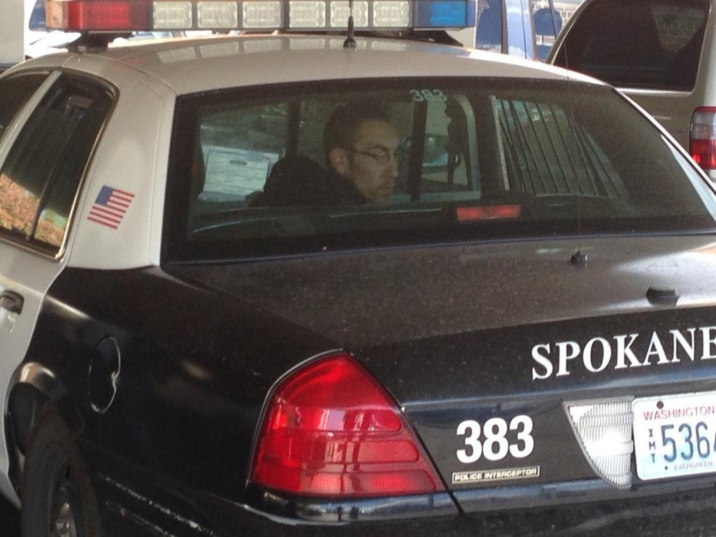 One of the three men arrested in connection to two coffee stand robberies sits in the back of a Spokane Police Department patrol car.