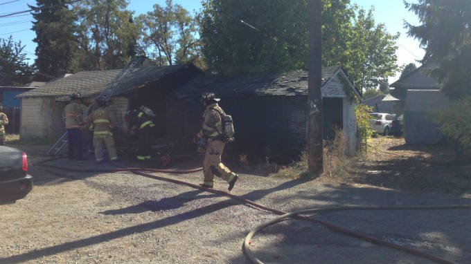 One garage was destroyed and another damaged after a pile of debris caught fire Monday morning in north Spokane.