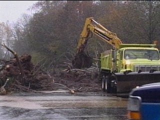 A backhoe clears debris from a road in Skokomish, Washington