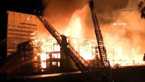 More than 250 firefighters doused the flames at a construction site that consumed the wood-framed structure and damaged three floors of an adjacent high-rise.