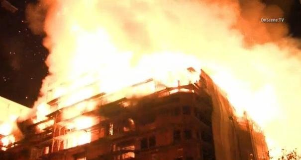 Investigators want to question two potential witnesses who were near a downtown Los Angeles fire last week that reduced an apartment construction site to ashes.
