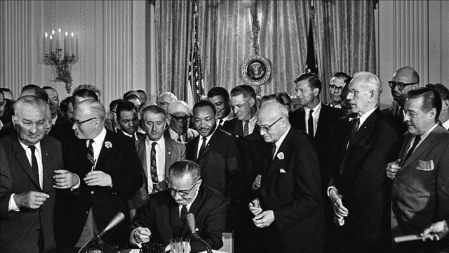 President Johnson signs the 1964 Civil Rights Act with Martin Luther King.
