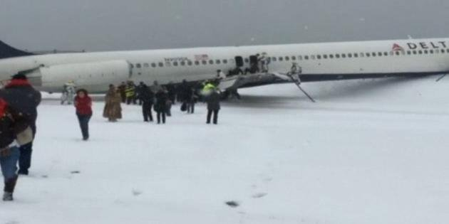 A plane from Atlanta skidded off a runway at LaGuardia Airport while landing Thursday, crashing through a chain-link fence and coming to rest with its nose perilously close to the edge of an icy bay.