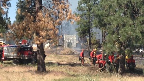 A five acre brush fire destroyed a garage Thursday near Airway Heights