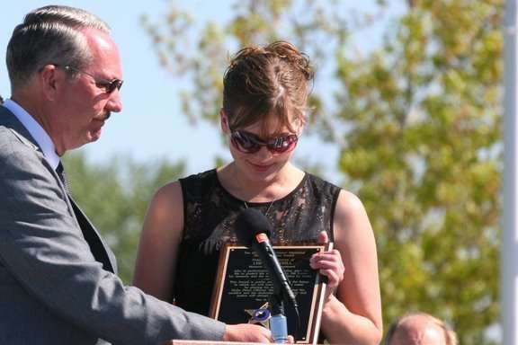 Christina Newbill receives a plaque on behalf of her father